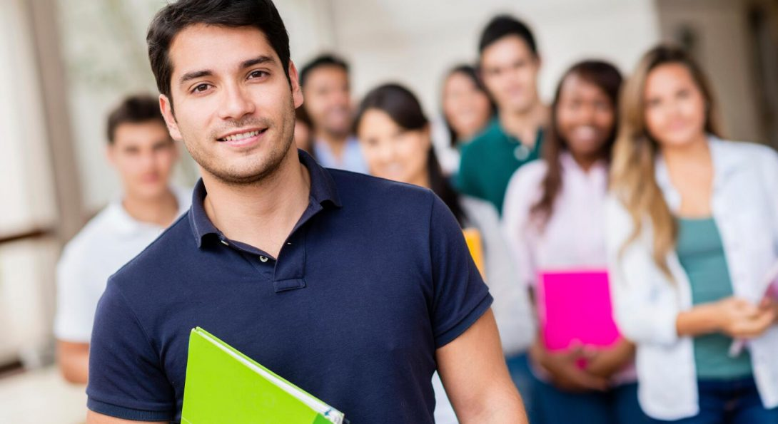 Young man, holding a green notebook smiling with other students in the background
